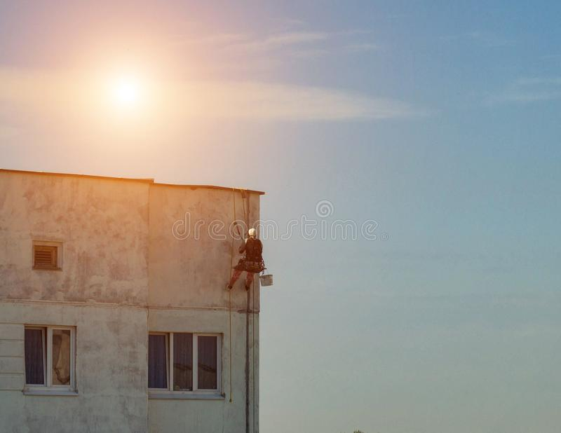 Male construction climber repairs the leaky seams in the panel house, the sun, alpinist royalty free stock photography