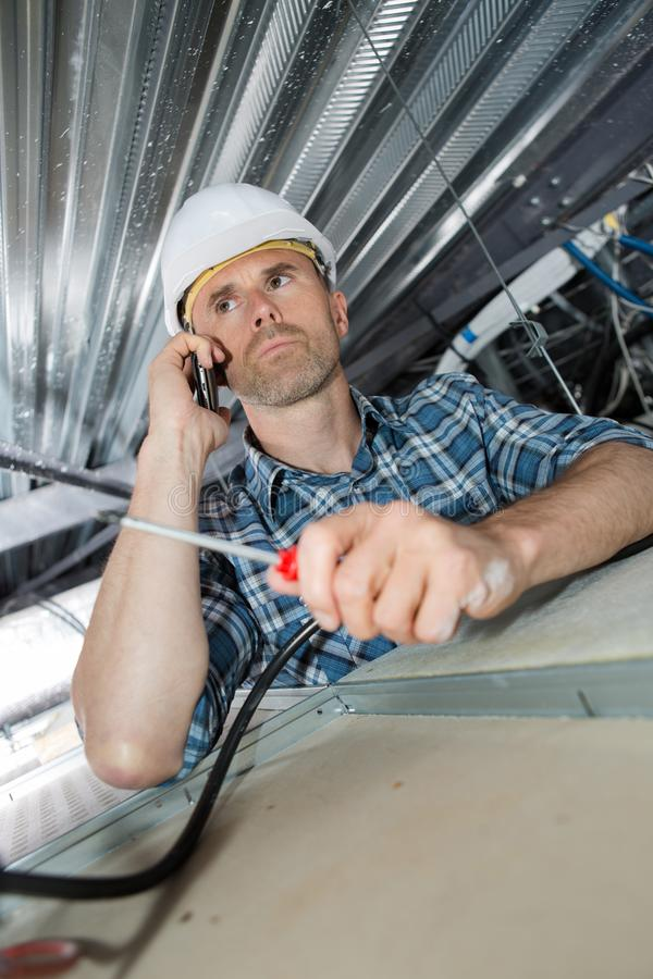 Male construction worker builder on cell phone in building ceiling stock photo