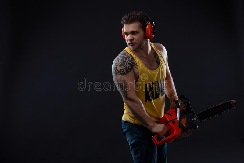 Male construction worker with chainsaw. Portrait of a strong muscular man. Young handsome builder. Male with electric saw. ma stock photography