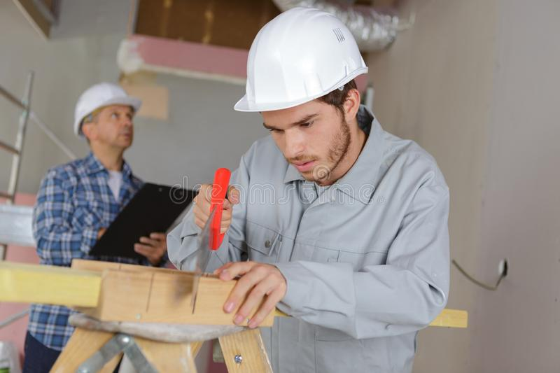 Male construction worker cutting wood with handsaw royalty free stock photography