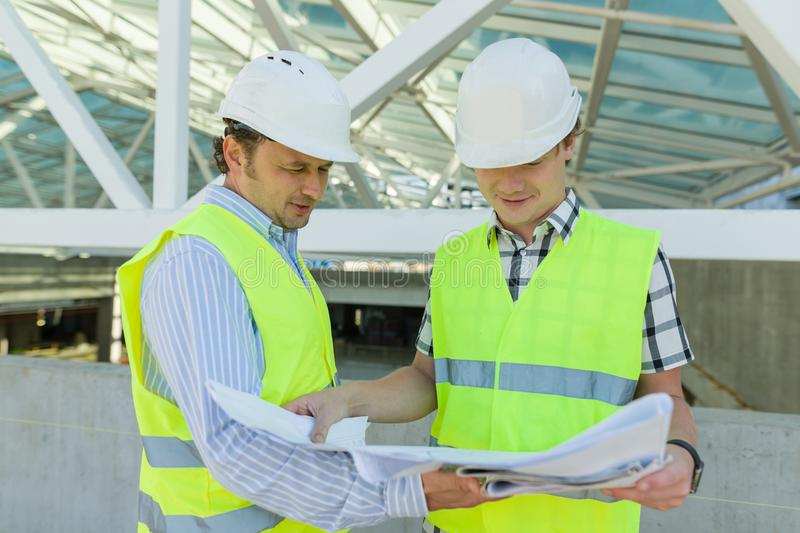 Male construction worker and engineer at the construction site. Building, development, teamwork and people concept royalty free stock images