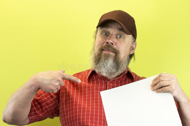 Male construction worker holding blank advertising board. Construction worker with poster. A rude, bearded, stern man in a red shi. Rt and a baseball cap shows a stock images