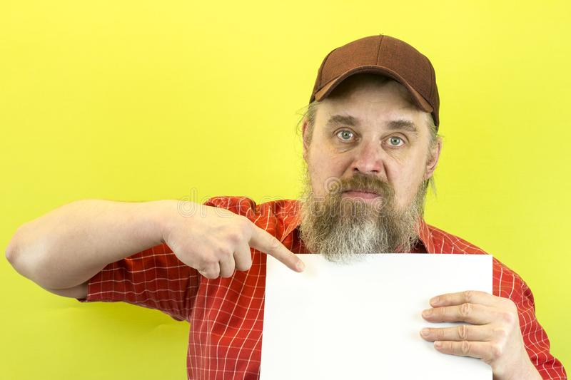 Male construction worker holding blank advertising board. Construction worker with poster. A rude, bearded, stern man in a red shi. Rt and a baseball cap shows a stock photos
