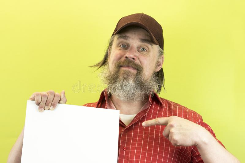 Male construction worker holding blank advertising board. Construction worker with poster. A rude, bearded, stern man in a red shi. Rt and a baseball cap shows a royalty free stock photos