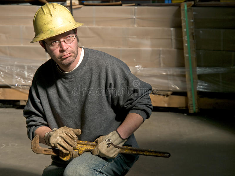 Male Construction Worker with large pipe wrench on Knee. Posed kneeling in warehouse stock photo