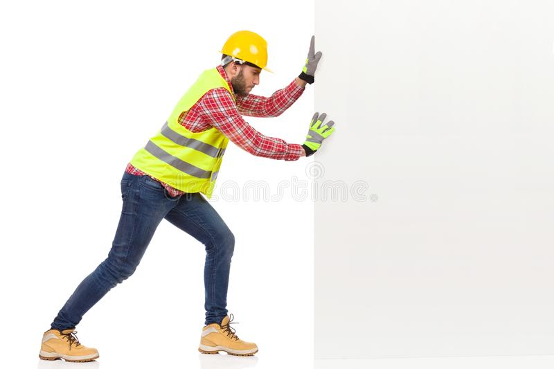 Male Construction Worker Is Pushing A White Wall. Man In Reflective Vest And Yellow Helmet Is Pushing A White Wall. e View. Full Length Studio Shot Isolated On stock photography