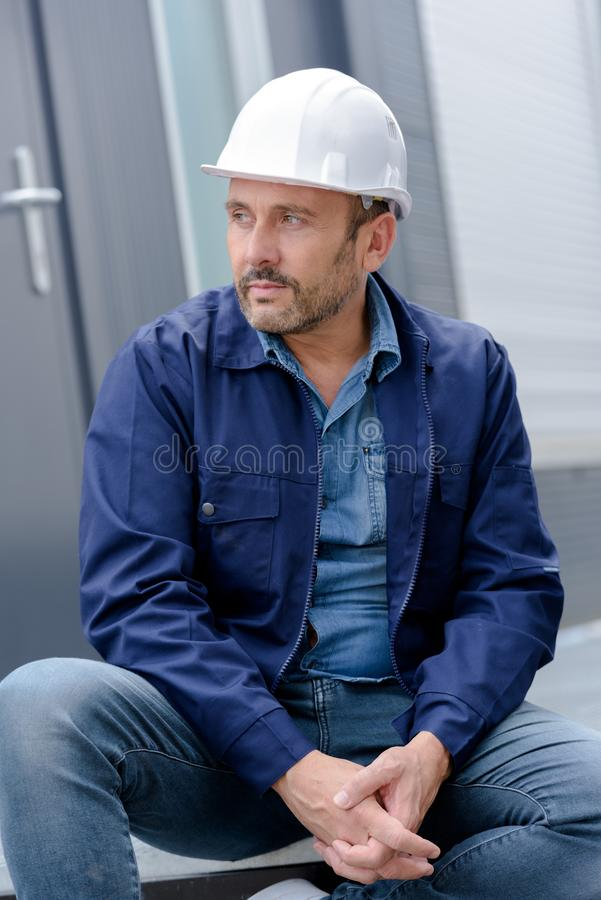Male construction worker in safety helmet sitting stock photography
