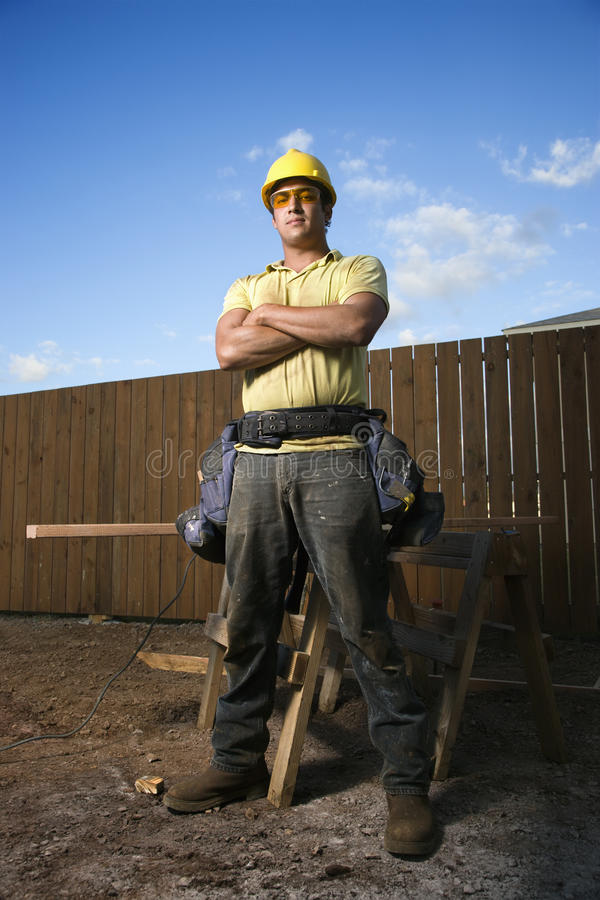 Male Construction Worker Stands with Folded Arms. Male Caucasian construction worker stands confidently and looks into the camera. His arms are folded across his royalty free stock photos