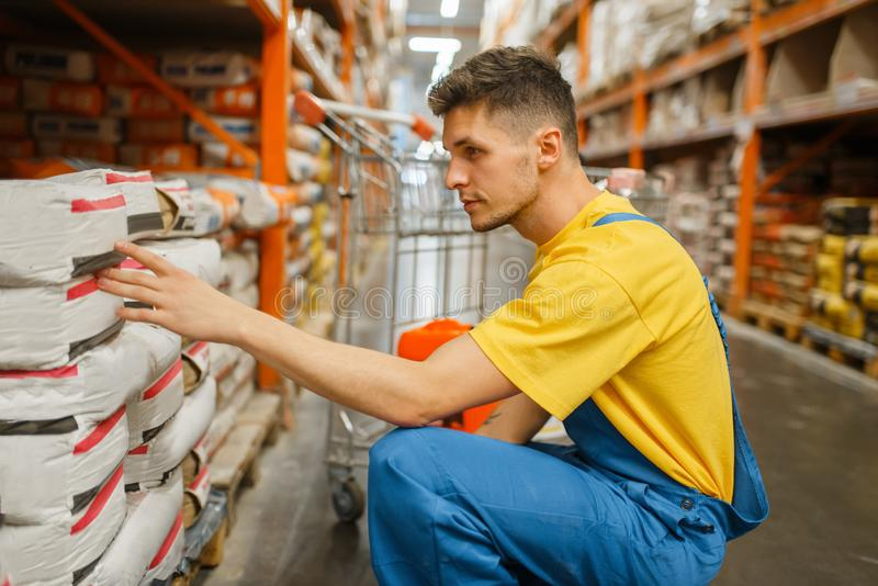 Male constructor choosing cement in hardware store stock photography