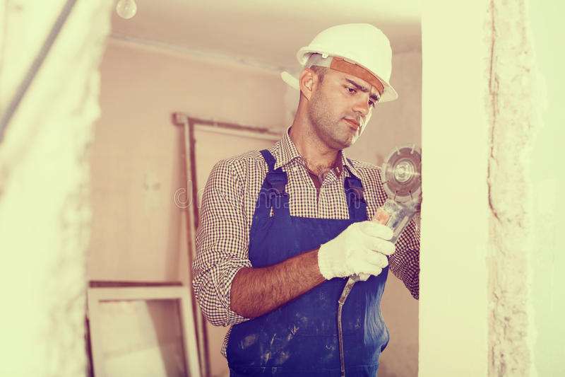 Male constructor with circular saw in gloves stock photo