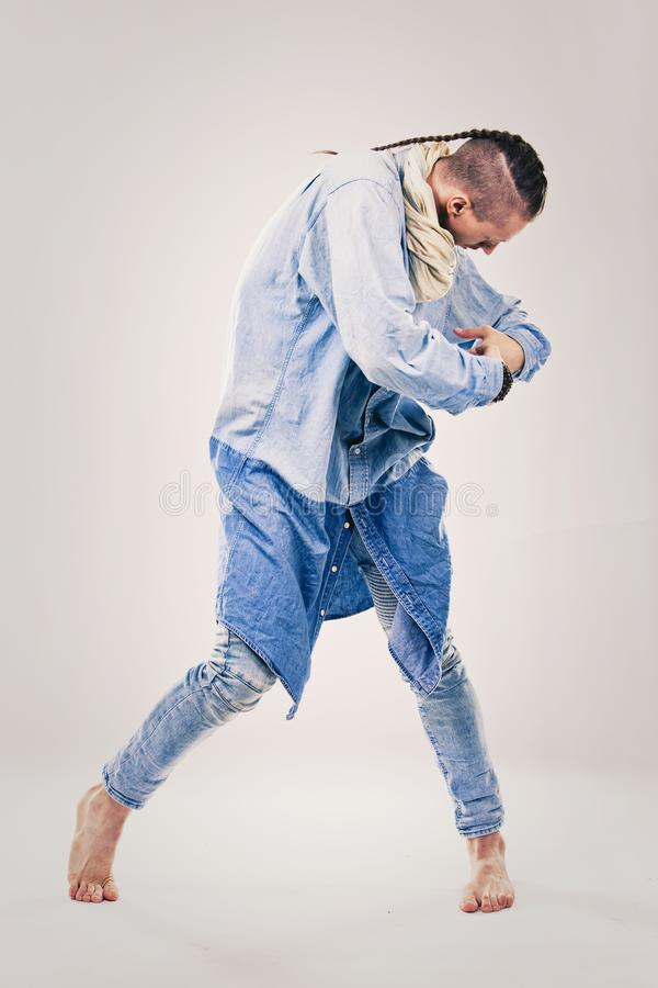 Male contemporary hip hop dancer in denim. Caucasian male dancer wearing blue denim shirt and pants on light background performing hip hop and contemporary style royalty free stock image