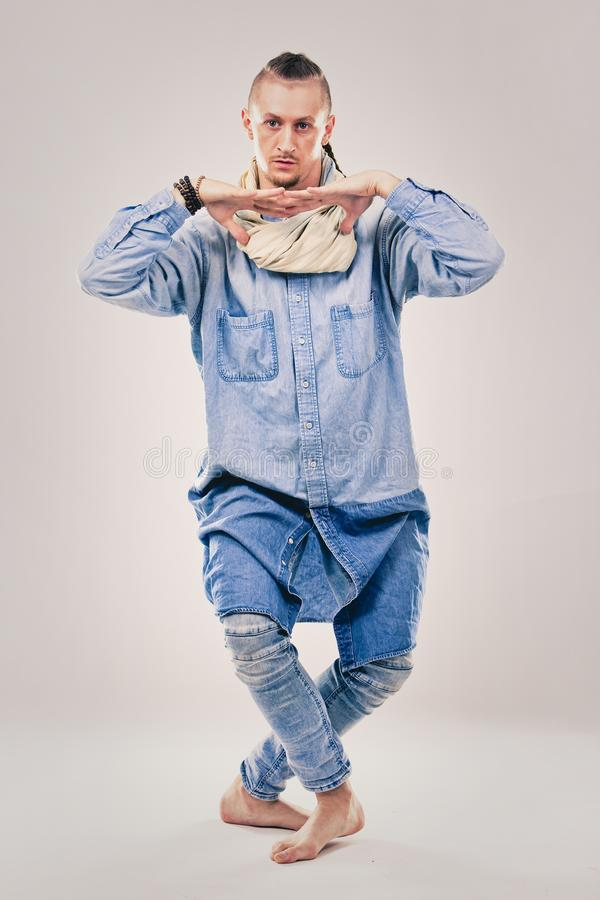 Male contemporary hip hop dancer in denim. Caucasian male dancer wearing blue denim shirt and pants on light background performing hip hop and contemporary style royalty free stock photo