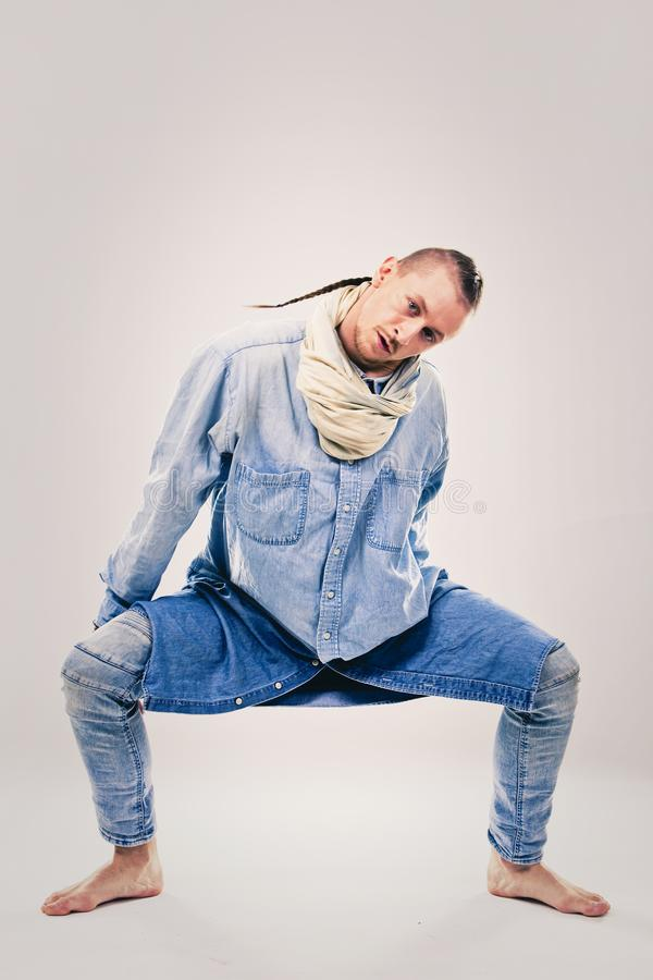Male contemporary hip hop dancer in denim. Caucasian male dancer wearing blue denim shirt and pants on light background performing hip hop and contemporary style stock images