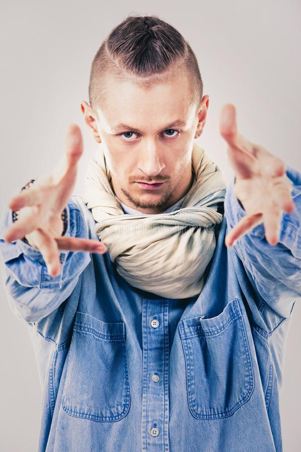 Male contemporary hip hop dancer in denim. Caucasian male dancer wearing blue denim shirt and pants on light background performing hip hop and contemporary style stock photography
