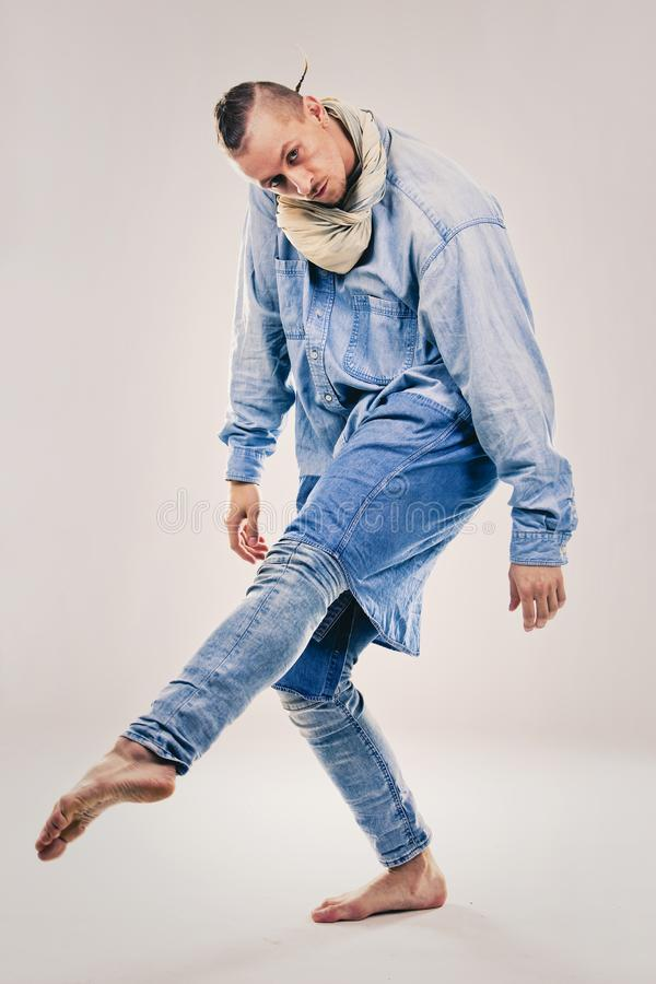 Male contemporary hip hop dancer in denim. Caucasian male dancer wearing blue denim shirt and pants on light background performing hip hop and contemporary style royalty free stock photography