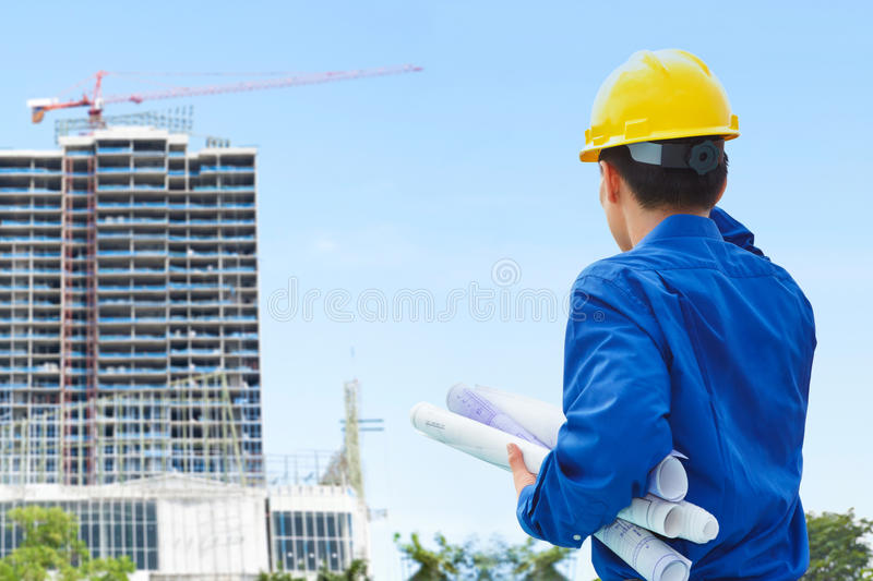 Male contractor and bulding project. Male contractor or civil engineer looking at the building project on progress stock image