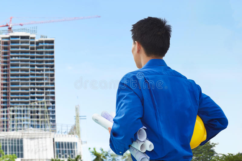 Male contractor and bulding project. Male contractor or civil engineer looking at the building project on progress stock photos