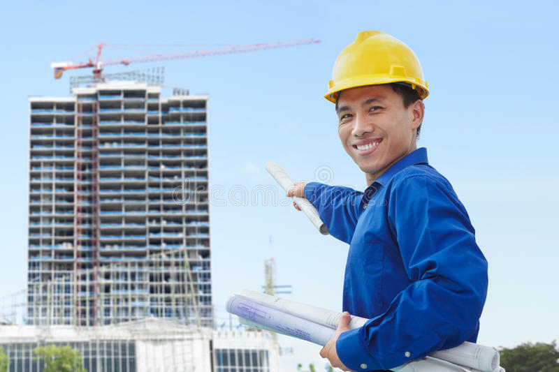 Male contractor and bulding project. Male contractor or civil engineer looking at the building project on progress royalty free stock photos