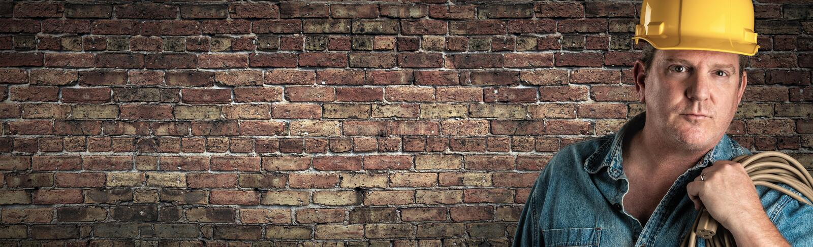 Male Contractor In Hard Hat Holding Cable In Front Of Old Brick Wall Banner with Copy Space.  stock images