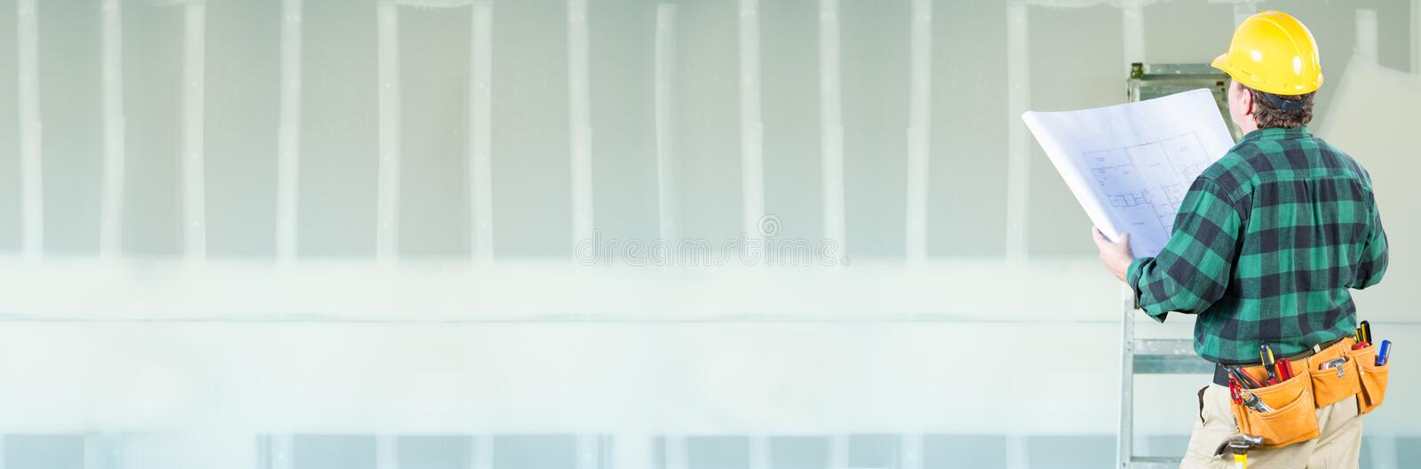 Male Contractor Wearing Hard Hat Facing Drywall Banner Background with Ladder stock image