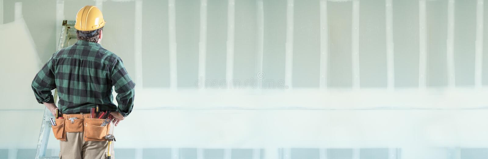 Male Contractor Wearing Hard Hat Facing Drywall Banner Background with Ladder royalty free stock image