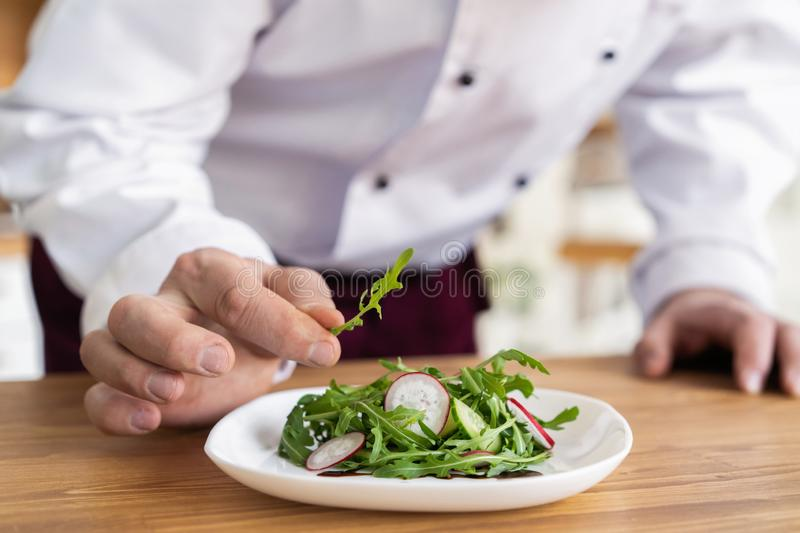 Male cook chef decorating garnishing prepared salad dish on the plate in restaurant commercial kitchen. royalty free stock photo