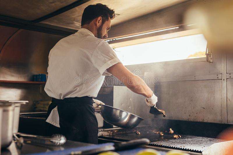 Male cook preparing a dish in food truck. Male cook making some food in a food truck parked under a tree. Man chopping vegetable on his food truck royalty free stock photo