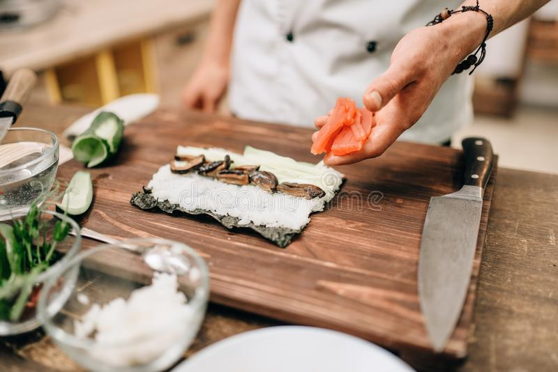 Male cook making sushi on wooden table, asian food. Traditional japanese cuisine, preparation process stock photography