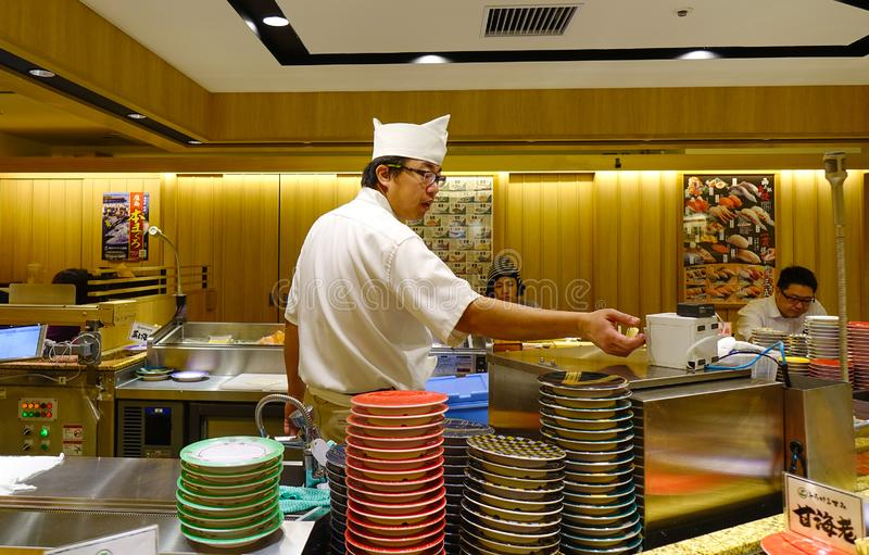 A male cook prepares sushi in the restaurant stock images
