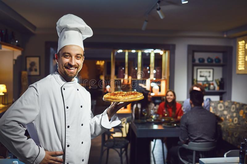 A male cook is smiling against the background of a restaurant. A male cook is smiling against the background of people at a table in a restaurant stock photography