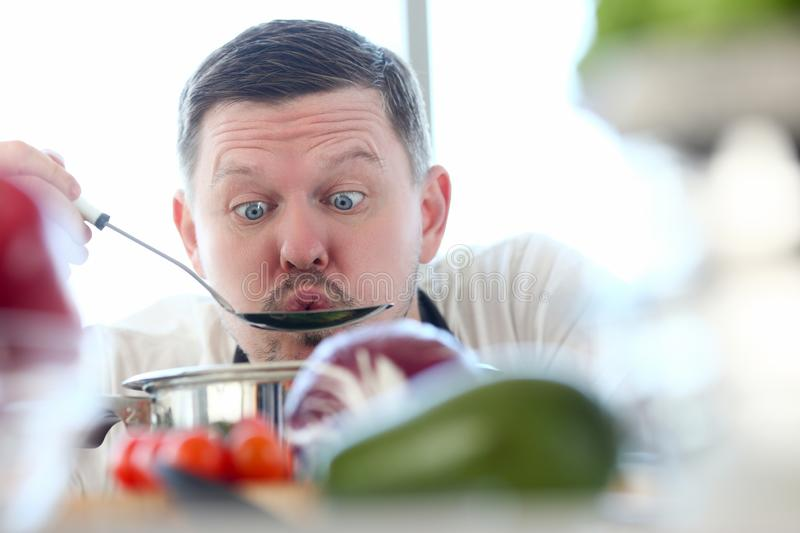 Male cook tries hot soup from pan. Blowing on him to cool concept against background of kitchen stock photography