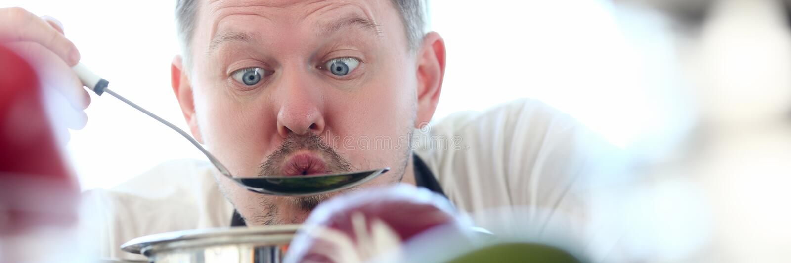 Male cook tries hot soup from pan. Blowing on him to cool concept against background of kitchen stock images