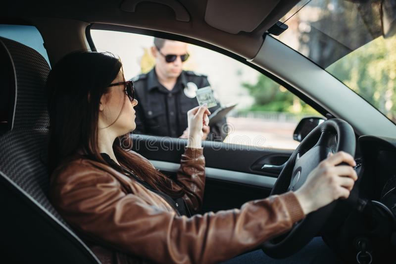 Male cop in uniform writes a fine to female driver. Law protection, car traffic inspector, safety control job royalty free stock photography