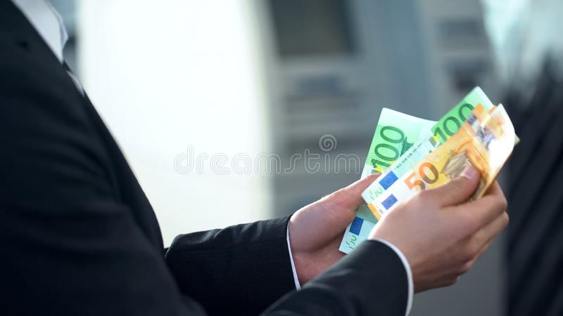 Male counting euros withdrawn from ATM, good service, business trip to Europe stock photos