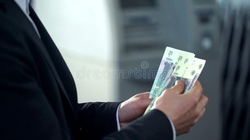 Male counting rubbles withdrawn from ATM, good service, business trip to Russia stock photography