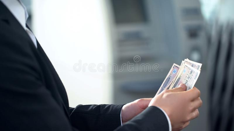Male counting Yens withdrawn from ATM, good service, business trip to Japan. Stock photo royalty free stock images