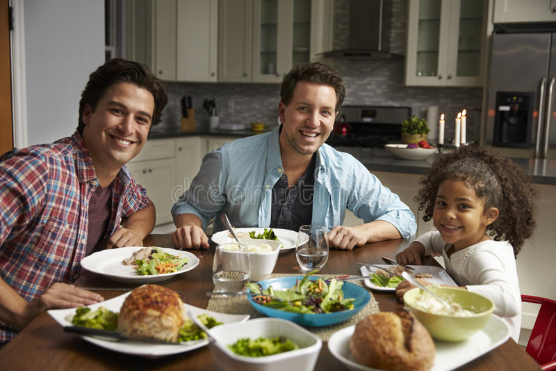 Male couple and black daughter dining at home look to camera stock images