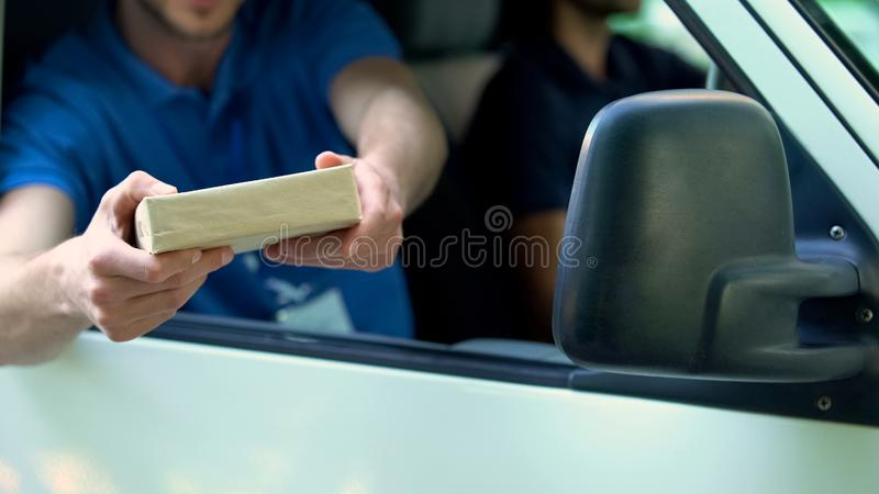 Male courier arriving in post van and giving package, same day express delivery royalty free stock images