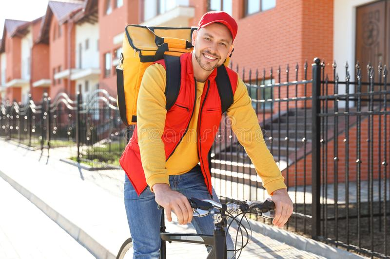 Male courier on bicycle delivering food. In city royalty free stock images
