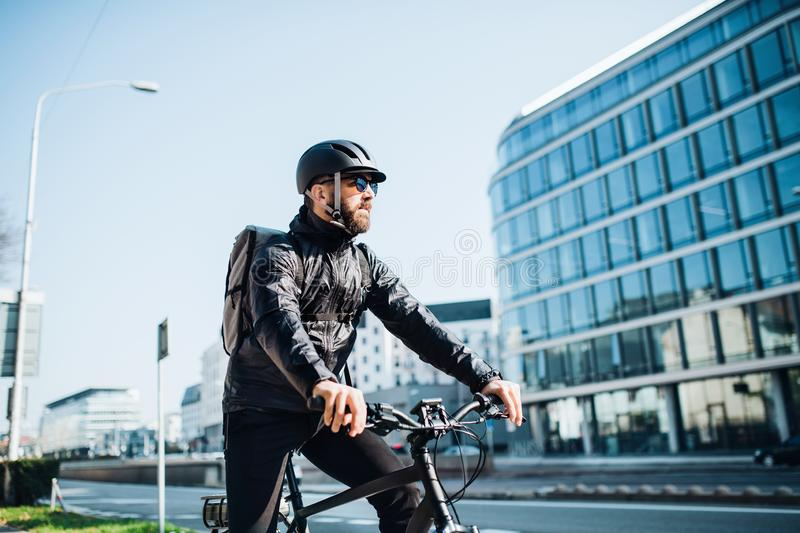 Male courier with bicycle delivering packages in city. Copy space. Male hipster courier with bicycle cycling on a road in city, delivering packages. Copy space stock photo