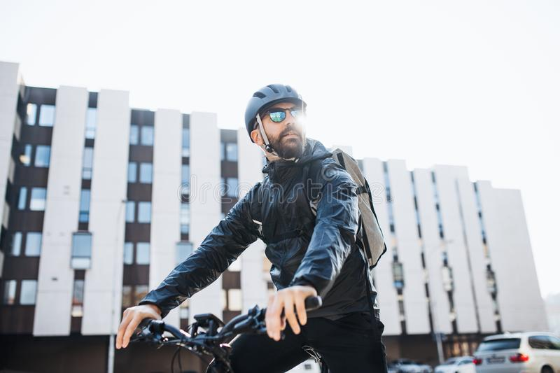 Male courier with bicycle and sunglasses delivering packages in city. Copy space royalty free stock images