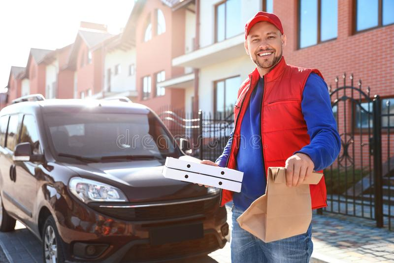 Male courier delivering  in city on sunny day royalty free stock photography