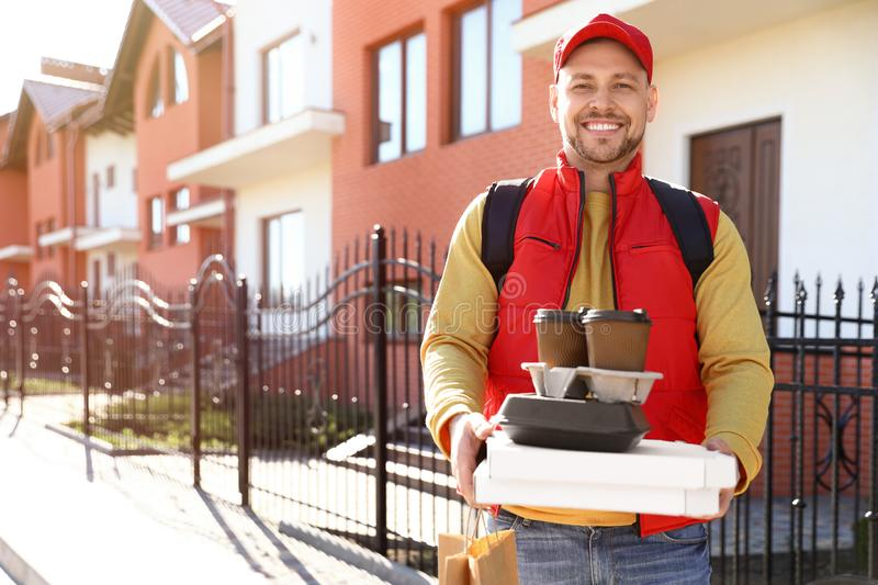 Male courier delivering food in city on sunny royalty free stock image