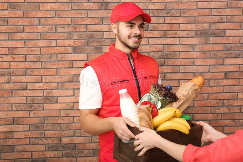 Male courier delivering food to client. Indoors stock photo