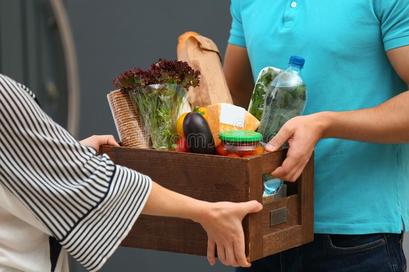 Male courier delivering food to client, closeup. Male courier delivering food to client indoors, closeup stock photography