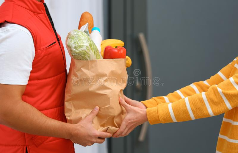 Male courier delivering food to client, closeup. Male courier delivering food to client indoors, closeup royalty free stock image