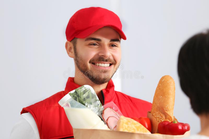 Male courier delivering food to client. On light background stock photo
