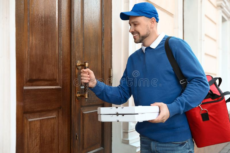 Male courier with order at entrance royalty free stock images