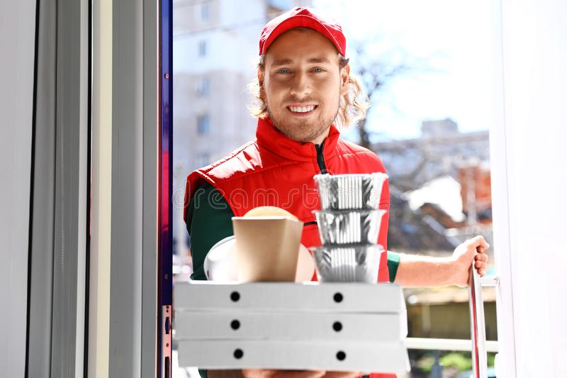 Male courier with order at open door. Food delivery stock images