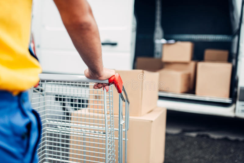 Male courier in uniform work with cargo, back view. Male courier in uniform works with cargo, back view. Truck with parcels on background. Distribution business stock photography